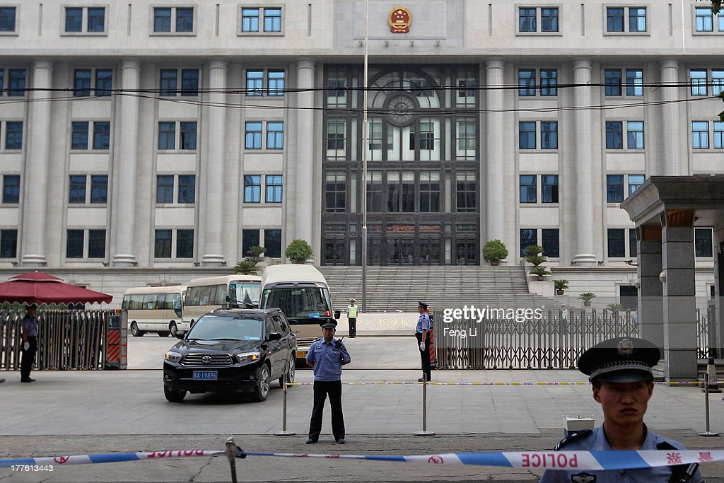 Chinese policemen guard as vehicles leaving after the fourth day of former Chinese politician Bo Xilai's trial at Jinan Intermediate People's Court on August 25, 2013 in Jinan, China. Ousted Chinese politician Bo Xilai is standing trial on charges of bribery, corruption and abuse of power for a third day. Bo Xilai made global headlines last year when his wife Gu Kailai was charged and convicted of murdering British businessman Neil Heywood.