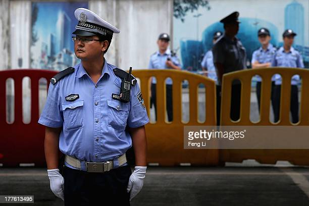 Chinese policemen guard outside the Jinan Intermediate People's Court during the fourth day of former Chinese politician Bo Xilai's trial on August...