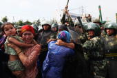 Chinese policemen push Uighur women who are protesting at a street on July 7 2009 in Urumqi the capital of Xinjiang Uighur autonomous region China...