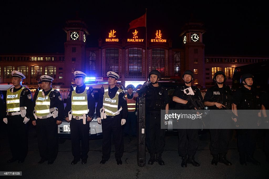Chinese policemen take up position during a drill outside the railway station in Beijing on the early hours of May 2, 2014. Chinese President Xi Jinping ordered a crackdown after a stabbing spree and explosion at a railway station in the restive Muslim-majority region of Xinjiang left two attackers and a civilian dead and 79 wounded, state media said. CHINA