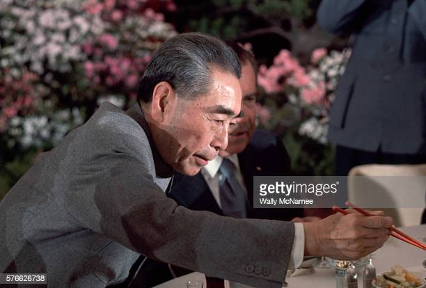 Chinese Premier Chou EnLai reaches for food with chopsticks at an official banquet held in the Great Hall of the People during Richard Nixon's visit...