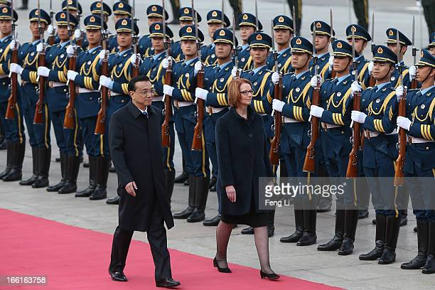 Chinese Premier Li Keqiang accompanies Australian Prime Minister Julia Gillard to view an honour guard during a welcoming ceremony outside the Great...