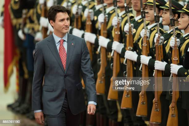 Chinese Premier Li Keqiang accompanies Canada's Prime Minister Justin Trudeau to view an honour guard during a welcoming ceremony inside the Great...