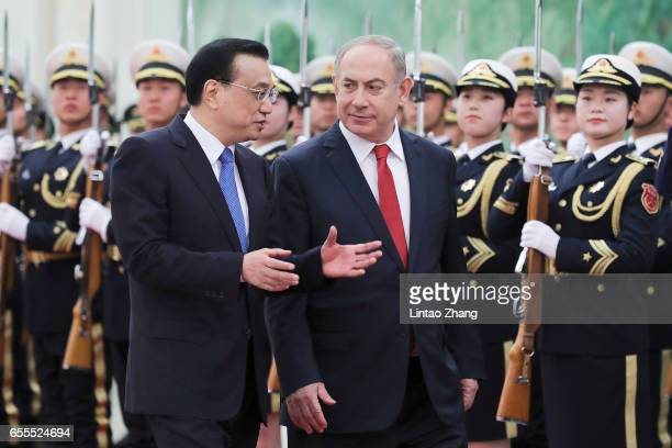 Chinese Premier Li Keqiang accompanies Israel Prime Minister Benjamin Netanyahu to view an honour guard during a welcoming ceremony inside the Great...