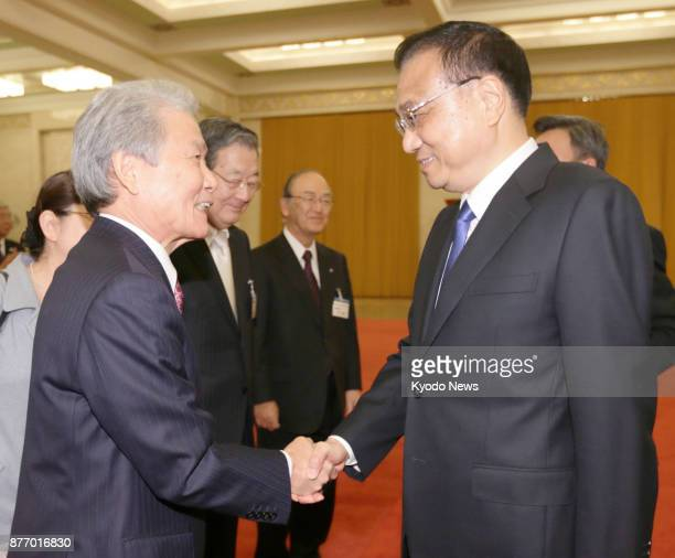 Chinese Premier Li Keqiang and Japan Business Federation Chairman Sadayuki Sakakibara shake hands before their talks at the Great Hall of the People...