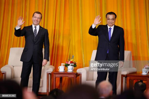 Chinese Premier Li Keqiang and Russian Prime Minister Dmitry Medvedev wave after the closing ceremony of a ChinaRussia media cooperation program at...