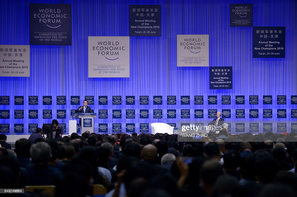 Chinese Premier Li Keqiang (L) answers a question as founder and executive chairman of the World Economic Forum, Klaus Schwab (R), listens on the first day of the World Economic Forum in Tianjin on June 27, 2016. The annual World Economic Forum New Champions meeting brings together business, economic and political leaders. / AFP / POOL / WANG