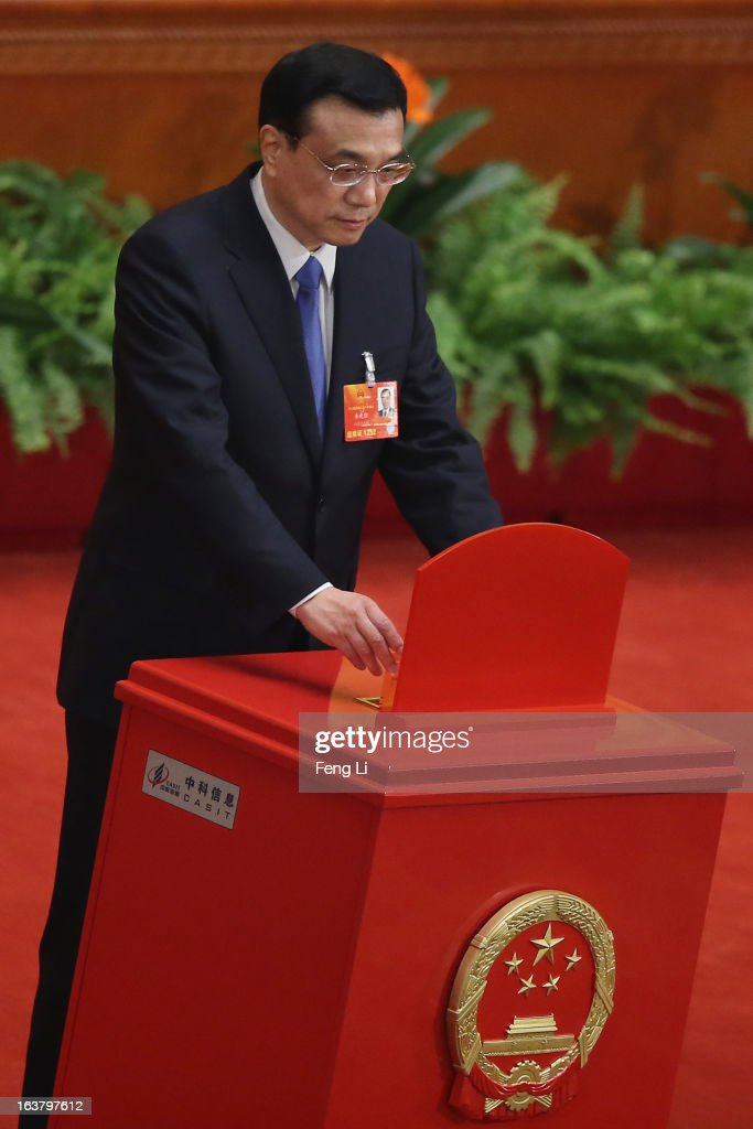 Chinese Premier Li Keqiang casts his vote into a box during the sixth plenary meeting of the National People's Congress at the Great Hall of the People on March 16, 2013 in Beijing, China. The new lineup of China's State Council, nominated by Premier Li Keqiang, was endorsed by lawmakers at the ongoing national legislative session Saturday afternoon.