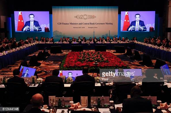Chinese Premier Li Keqiang delivers a message as seen on large video screens to delegates of the G20 Finance Ministers and Central Bank Governors...