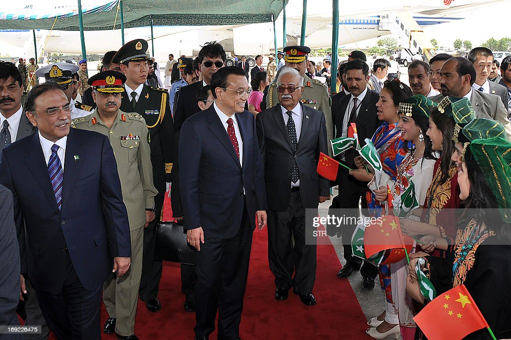 Chinese Premier Li Keqiang (C), flanked by Pakistani President Asif Ali Zardari (L) and caretaker premier Mir Hazar Khan Khoso (centre R) is welcomed by hostesses bearing Chinese flags upon his arrival at Pakistan's Nur Khan air base in Rawalpindi on May 22, 2013. Chinese Premier Li Keqiang vowed to strengthen his country's partnership with Pakistan as he arrived on May 22 for a visit less than two weeks after the country's general election. The long-time allies will look to use the two-day trip to boost trade ties, and Li will meet prime minister-elect Nawaz Sharif -- who has not yet been sworn in -- as well as holding talks with senior officials.