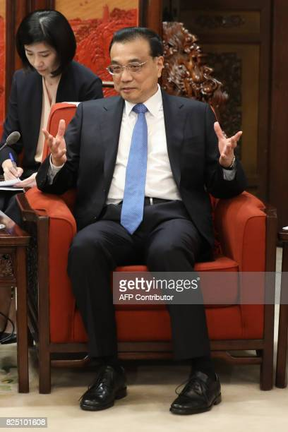 Chinese Premier Li Keqiang gestures as he speaks with Michigan Governor Rick Snyder during a meeting at the Zhongnanhai Leadership Compound in...