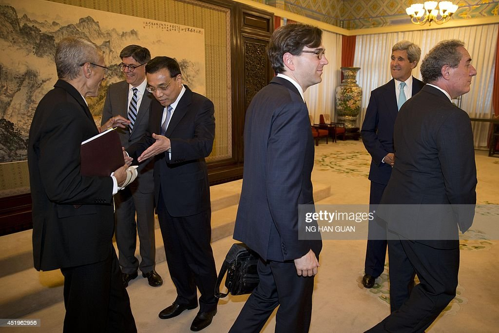 Chinese Premier Li Keqiang (3rd-L) gestures at the bandaged hand of White House senior counselor John Podesta (L) as US Secretary of State John Kerry and US Treasury Secretary Jacob Lew (2nd-L) arrive at a meeting held at the Zhongnanhai leadership compound in Beijing on July 10, 2014. The US and China discussed trade and business concerns on July 10 -- with currencies and property rights among the thorny issues on the agenda -- as the world's two biggest economies held wide-ranging annual talks.