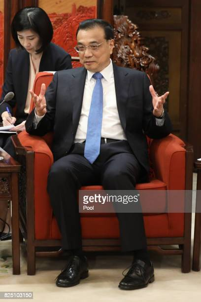 Chinese Premier Li Keqiang gestures to speak with Michigan Governor Rick Snyder during a meeting at the Zhongnanhai Leadership Compound on August 1...