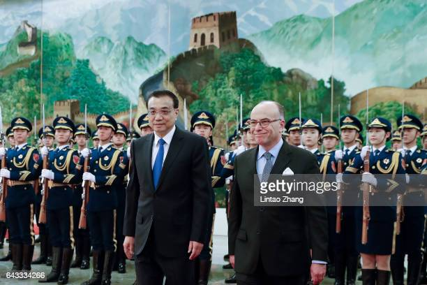 Chinese Premier Li Keqiang invites French Prime Minister Bernard Cazeneuve to view an honour guard during a welcoming ceremony inside the Great Hall...