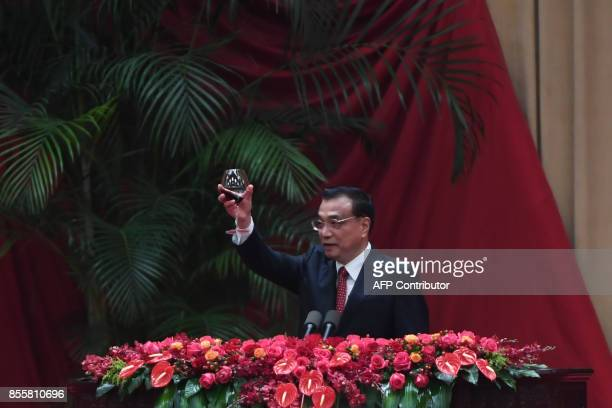 Chinese Premier Li Keqiang offers a toast during a reception on the eve of China's National Day which marks the 68th anniversary of the founding of...