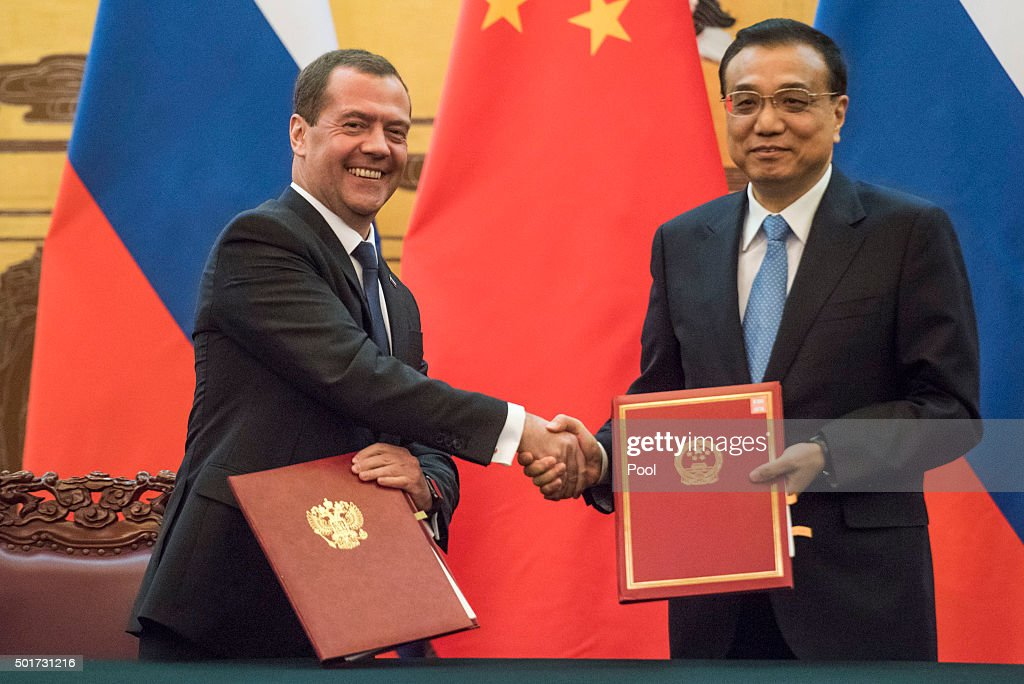 Chinese Premier Li Keqiang (R) shakes hand of Russian Prime Minister Dmitry Medvedev during a signature ceremony at the Great Hall of the People on December 17, 2015 in Beijing, China. Medvedev is on a 4-day visit to China.