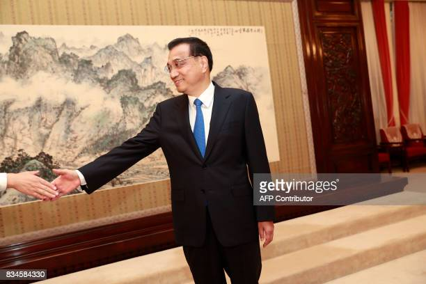 Chinese Premier Li Keqiang shakes hands with delegates during a meeting with Director general of World Health Organisation Tedros Adhanom Ghebreyesus...
