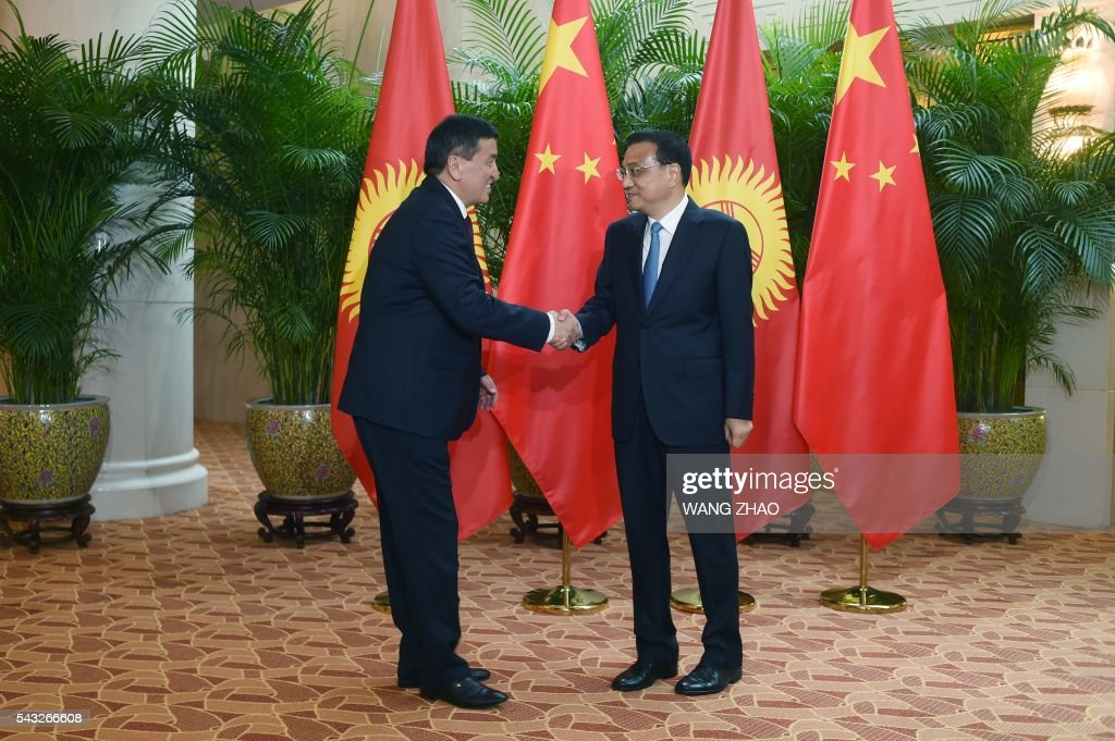Chinese Premier Li Keqiang (R) shakes hands with Kyrgyzstan's Prime Minister Temir Sariyev (L) during the World Economic Forum in Tianjin on June 27, 2016. The annual World Economic Forum New Champions meeting brings together business, economic and political leaders. ZHAO