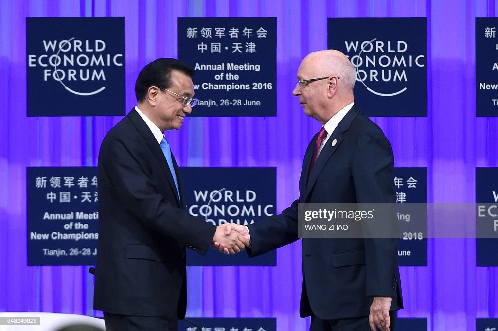 Chinese Premier Li Keqiang (L) shakes hands with the founder and executive chairman of the World Economic Forum, Klaus Schwab (R), on the first day of the World Economic Forum in Tianjin on June 27, 2016. The annual World Economic Forum New Champions meeting brings together business, economic and political leaders. / AFP / POOL / WANG