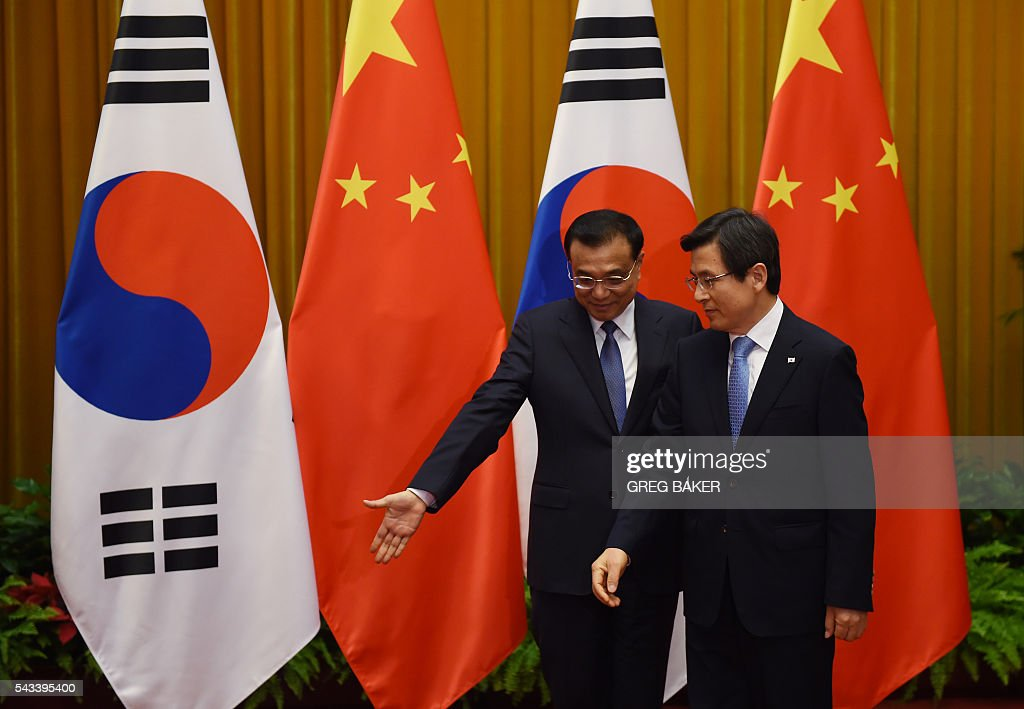 Chinese Premier Li Keqiang (L) shows South Korea's Prime Minister Hwang Kyo-ahn where to stand before they pose for photos ahead of their meeting at the Great Hall of the People in Beijing on June 28, 2016. / AFP / POOL / GREG