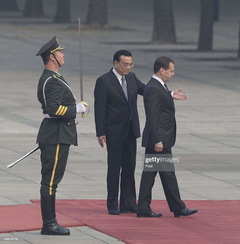 Chinese Premier Li Keqiang (C) shows the way to Russian Prime Minister Dmitry Medvedev (R) during a welcoming ceremony outside at the Great Hall of the People on October 22, 2013 in Beijing, China. Medvedev is in China on a two-day visit as a guest of Chinese Premier Li Keqiang to co-chair the 18th regular meeting between the Chinese and Russian heads of government.