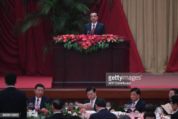 Chinese Premier Li Keqiang speaks as President Xi Jinping listens during a reception on the eve of China's National Day which marks the 68th...