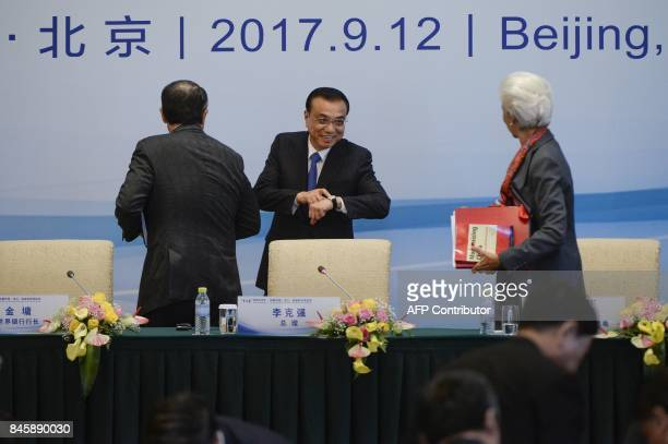 Chinese Premier Li Keqiang speaks to Managing Director of the International Monetary Fund Christine Lagarde as he points to his watch after a press...