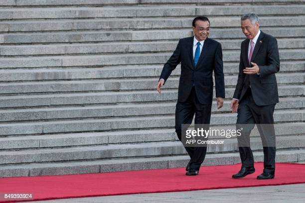 Chinese Premier Li Keqiang speaks with Singapore's Prime Minister Lee Hsien Loong during a welcome ceremony at the Great Hall of the People in...