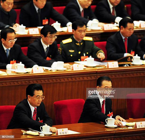 Chinese Premier Wen Jiabao and President Hu Jintao push a button to cast their vote after Wen made his speech at the opening session of the ruling...