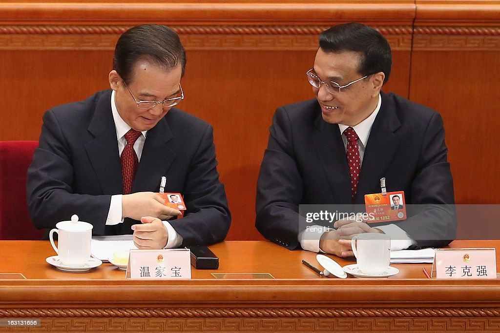 Chinese Premier Wen Jiabao (L) looks at his delegate card as Chinese Vice Premier Li Keqiang (Right) looks on after Wen delivered his work report at the opening session of the annual National People's Congress in Beijing's Great Hall of the People on March 5, 2013 in Beijing, China. Chinese Premier Wen Jiabao stressed Tuesday that the government should adopt effective measures to prevent and control pollution in response to people's expectations of having a good living environment.