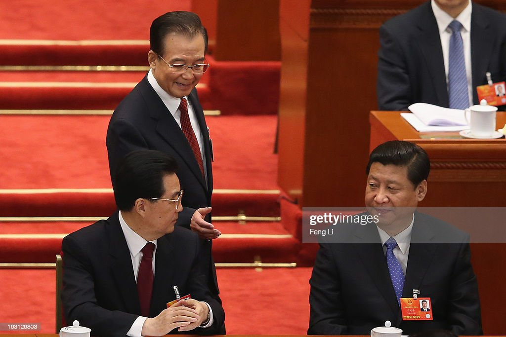 Chinese Premier Wen Jiabao (C) shakes hands with Chinese President Hu Jintao (L) as Chinese Communist Party General Secretary Xi Jinping (R) looks on after Wen delivered his work report at the opening session of the annual National People's Congress in Beijing's Great Hall of the People on March 5, 2013 in Beijing, China. Chinese Premier Wen Jiabao stressed Tuesday that the government should adopt effective measures to prevent and control pollution in response to people's expectations of having a good living environment.