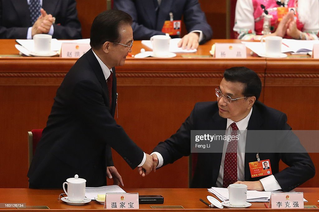 Chinese Premier Wen Jiabao (L) shakes hands with Chinese Vice Premier Li Keqiang (R) after Wen delivered his work report at the opening session of the annual National People's Congress in Beijing's Great Hall of the People on March 5, 2013 in Beijing, China. Chinese Premier Wen Jiabao stressed Tuesday that the government should adopt effective measures to prevent and control pollution in response to people's expectations of having a good living environment.