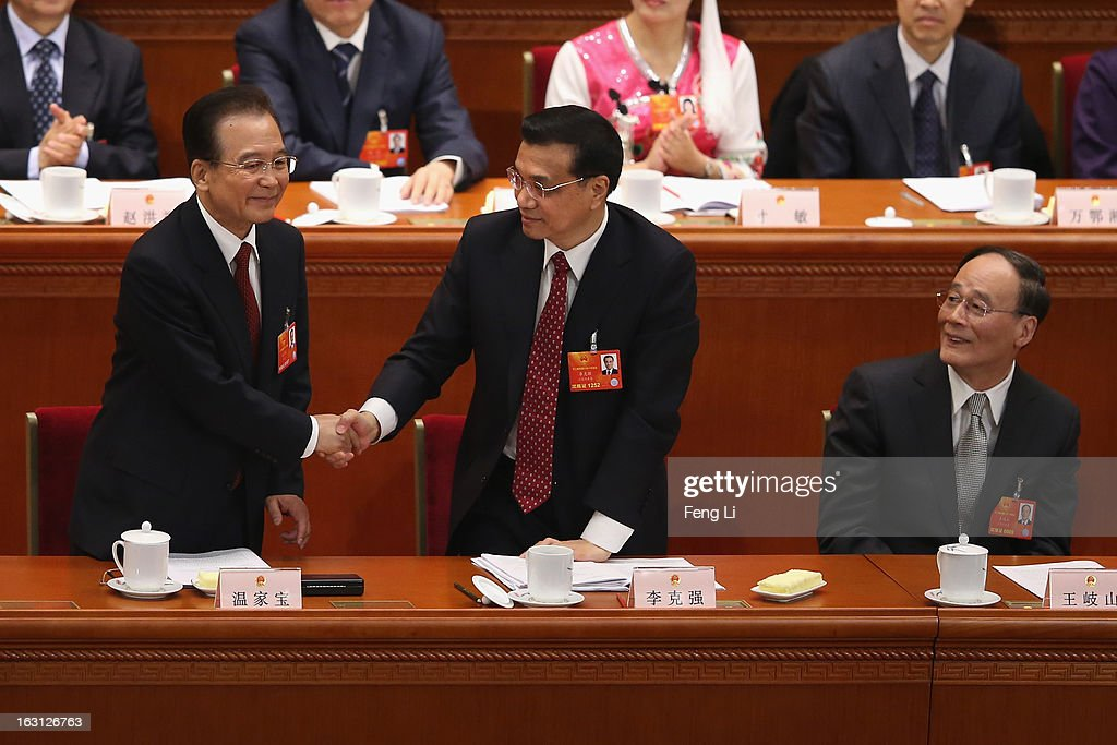 Chinese Premier <a gi-track='captionPersonalityLinkClicked' href=/galleries/search?phrase=Wen+Jiabao&family=editorial&specificpeople=204598 ng-click='$event.stopPropagation()'>Wen Jiabao</a> (L) shakes hands with Chinese Vice Premier <a gi-track='captionPersonalityLinkClicked' href=/galleries/search?phrase=Li+Keqiang&family=editorial&specificpeople=2481781 ng-click='$event.stopPropagation()'>Li Keqiang</a> (R) as Chinese Vice Premier <a gi-track='captionPersonalityLinkClicked' href=/galleries/search?phrase=Wang+Qishan&family=editorial&specificpeople=692964 ng-click='$event.stopPropagation()'>Wang Qishan</a> (R) looks on after Wen delivered his work report at the opening session of the annual National People's Congress in Beijing's Great Hall of the People on March 5, 2013 in Beijing, China. Chinese Premier <a gi-track='captionPersonalityLinkClicked' href=/galleries/search?phrase=Wen+Jiabao&family=editorial&specificpeople=204598 ng-click='$event.stopPropagation()'>Wen Jiabao</a> stressed Tuesday that the government should adopt effective measures to prevent and control pollution in response to people's expectations of having a good living environment.