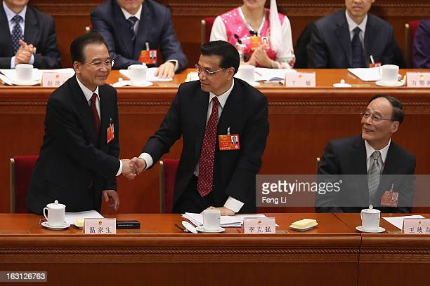 Chinese Premier Wen Jiabao shakes hands with Chinese Vice Premier Li Keqiang as Chinese Vice Premier Wang Qishan looks on after Wen delivered his...