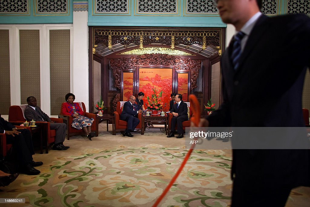 Chinese Premier Wen Jiabao speaks to South African President Jacob Zuma during their meeting while a security guard pulls a red rope to keep...