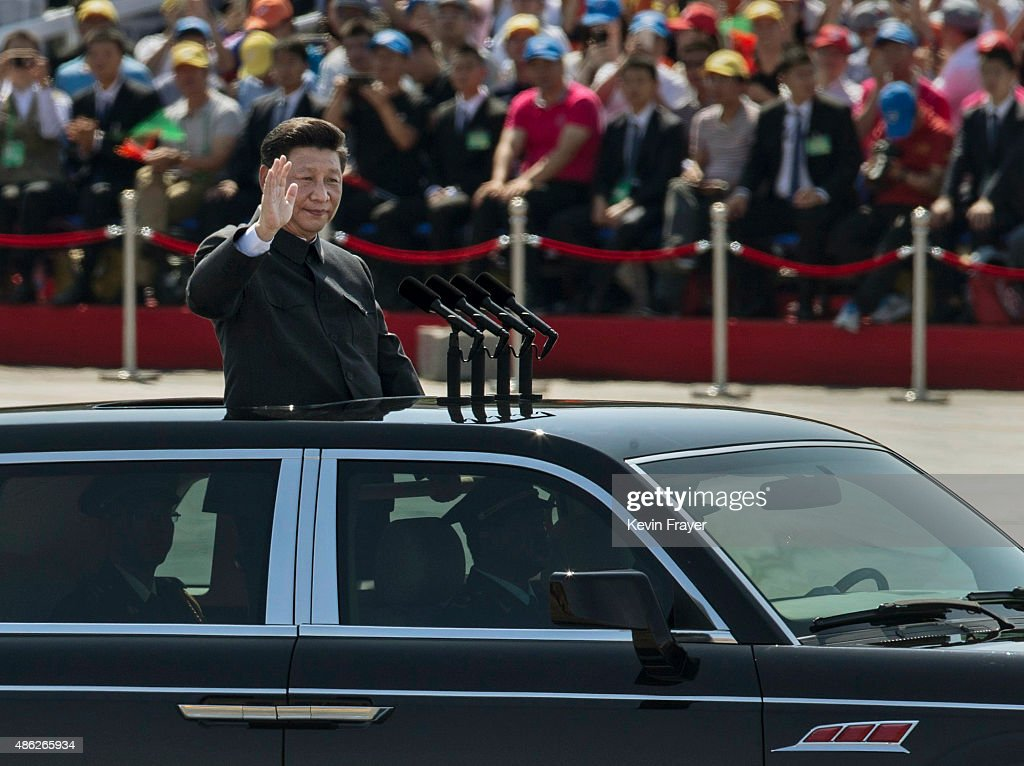 Chinese president and leader of the Communist Party Xi Jinping rides in an open top car as he greets soldiers and others in front of Tiananmen Square and the Forbidden City during a military parade on September 3, 2015 in Beijing, China. China is marking the 70th anniversary of the end of World War II and its role in defeating Japan with a new national holiday and a military parade in Beijing.