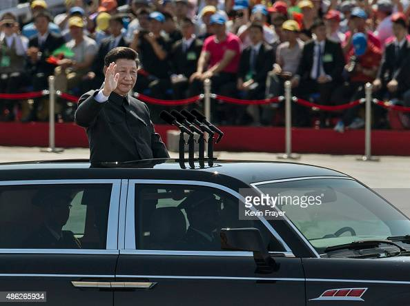 Chinese president and leader of the Communist Party Xi Jinping rides in an open top car as he greets soldiers and others in front of Tiananmen Square...