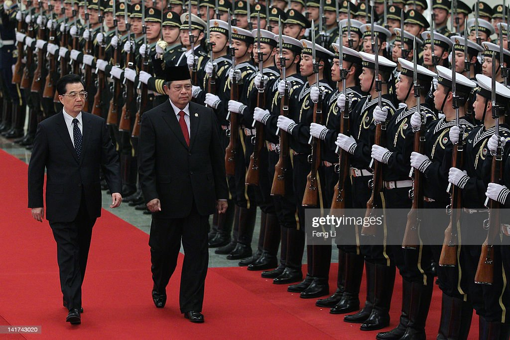 Chinese President Hu Jintao accompanies Indonesia's President Susilo Bambang Yudhoyono to view a guard of honour during a welcoming ceremony inside...