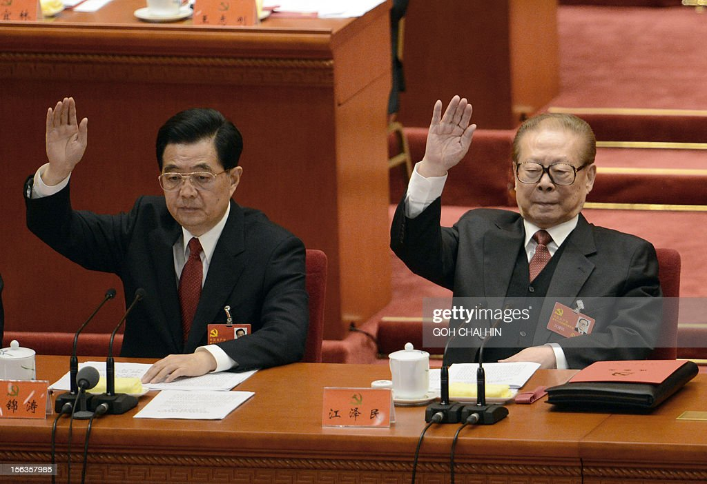 Chinese President Hu Jintao (L) and former president Jiang Zemin (R) raise their hands to vote for the reports at the closing of the 18th Communist Party Congress at the Great Hall of the People in Beijing on 14 November 2012. The week-long Communist Party Congress will end with a transition of power to Chinese Vice President Xi Jinping, who will govern for the coming decade amid growing pressure for reform of the communist regime's iron-clad grip on power. AFP PHOTO/GOH CHAI HIN