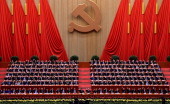 Chinese President Hu Jintao and former President Jiang Zemin with members of the Presidium raise the hands during the closing ceremony of the Party...