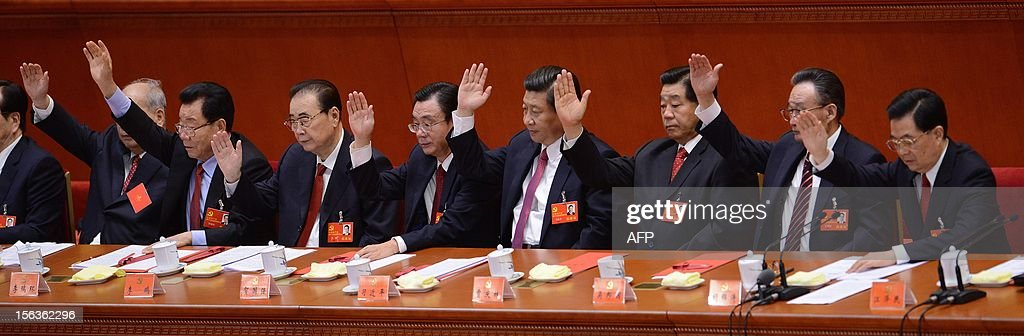 Chinese president Hu Jintao (R) and other Chinese leaders vote during the closing of the 18th Communist Party Congress at the Great Hall of the People in Beijing on 14 November, 2012. The week-long Communist Party Congress will end with a transition of power to Chinese Vice President Xi Jinping, who will govern for the coming decade amid growing pressure for reform of the communist regime's iron-clad grip on power. AFP PHOTO / WANG ZHAO