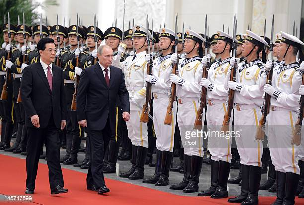 Chinese President Hu Jintao and Russian President Vladimir Putin review an honour guard during a welcoming ceremony for the Shanghai Cooperation...