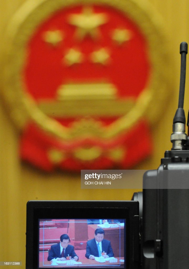 Chinese President Hu Jintao (L) and Vice President Xi Jinping are seen on a screen of a video camera at the opening session of the Chinese National People's Congress (NPC) at the Great Hall of the People in Beijing on March 5, 2013. China set its economic growth target for this year at 7.5 percent, unchanged on 2012, ahead of the opening on March 5 of the annual parliament session of the world's second-largest economy.