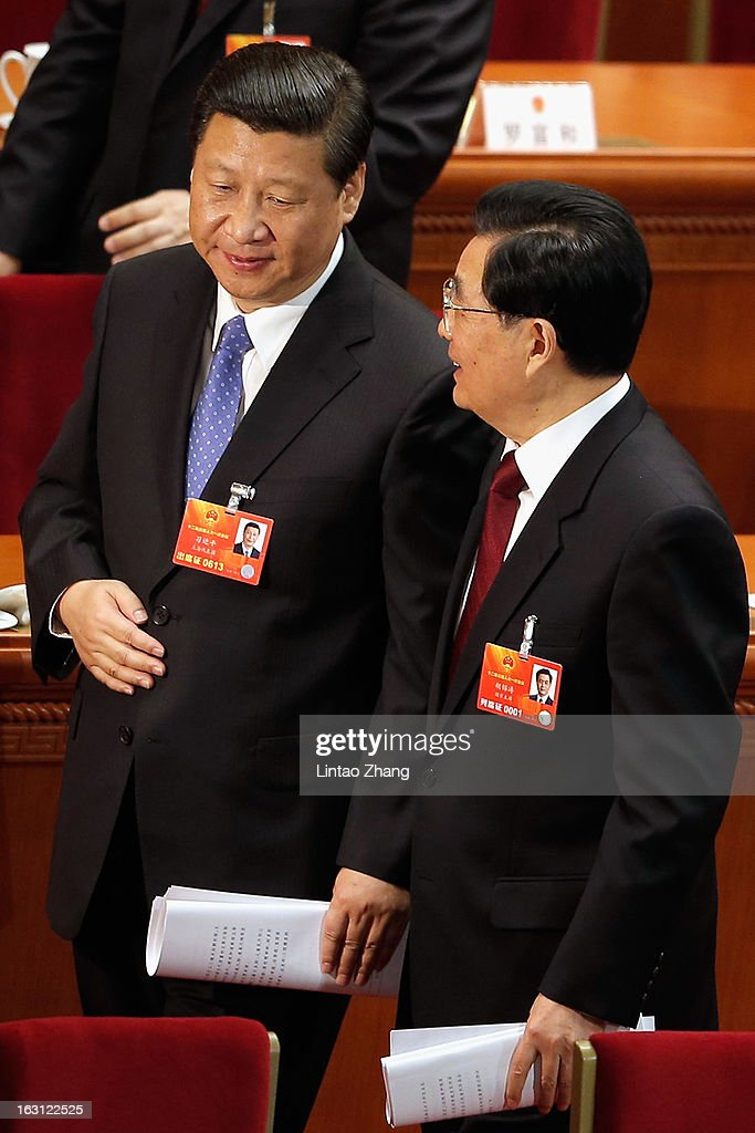 Chinese President Hu Jintao chats with Vice President Xi Jinping after the opening session of the annual National People's Congress at Great Hall of...