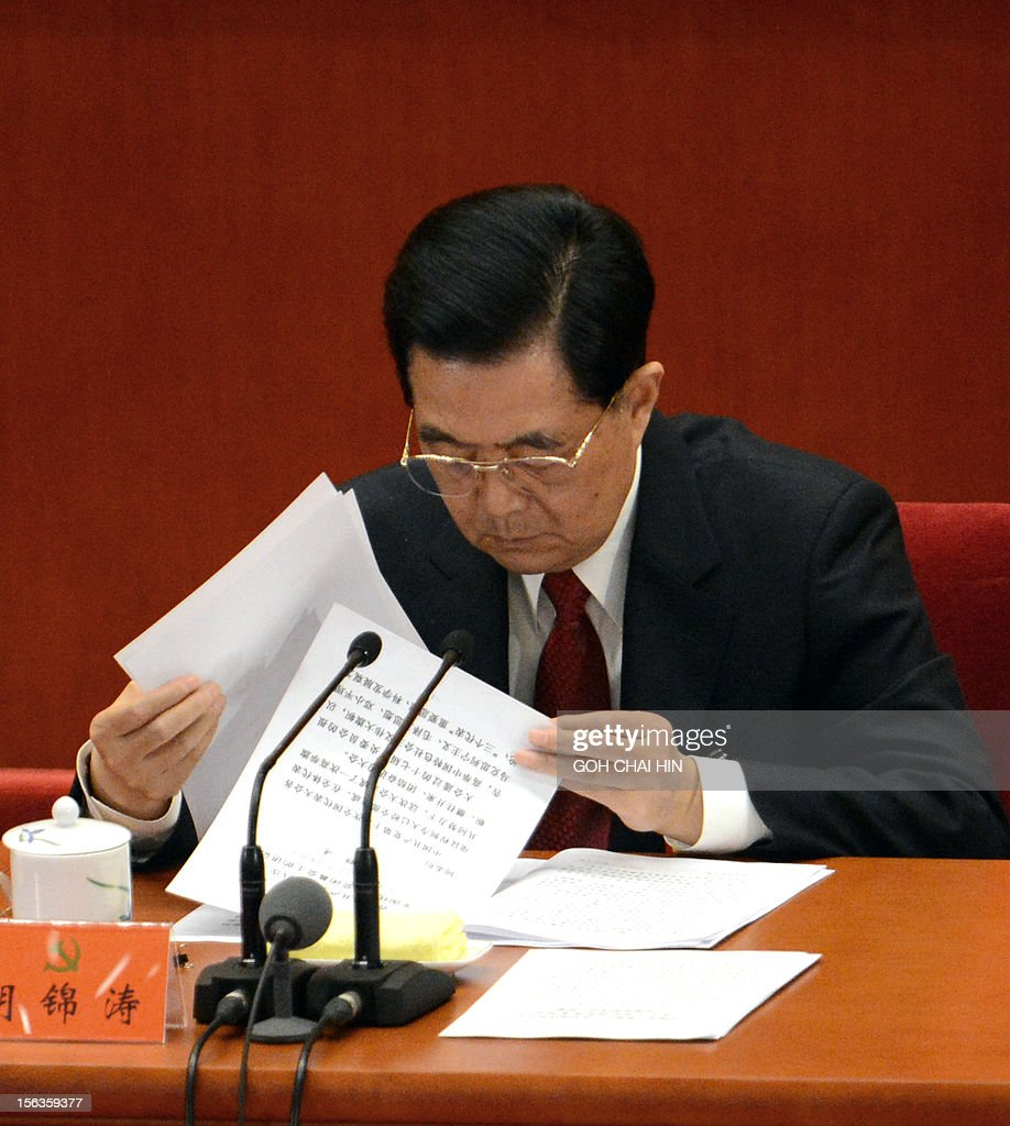 Chinese President Hu Jintao (C) checks through documents at the closing of the 18th Communist Party Congress at the Great Hall of the People in Beijing on 14 November 2012. The week-long Communist Party Congress will end with a transition of power to Chinese Vice President Xi Jinping, who will govern for the coming decade amid growing pressure for reform of the communist regime's iron-clad grip on power. AFP PHOTO/GOH CHAI HIN