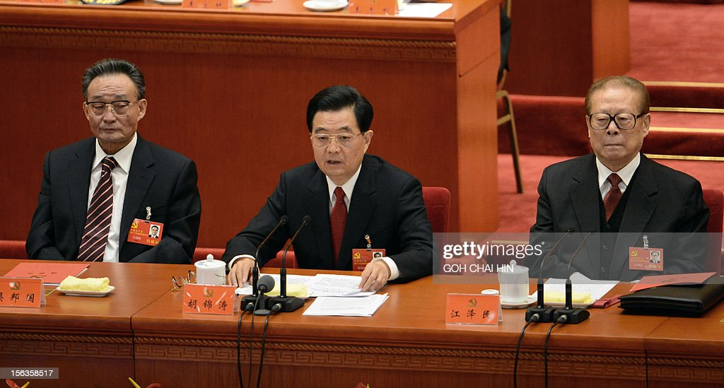 Chinese President Hu Jintao (C) flanked by former president Jiang Zemin (R) and NPC Chairman Wu Bangguo, delivers his final address at the closing of the 18th Communist Party Congress at the Great Hall of the People in Beijing on 14 November 2012. The week-long Communist Party Congress will end with a transition of power to Chinese Vice President Xi Jinping, who will govern for the coming decade amid growing pressure for reform of the communist regime's iron-clad grip on power.