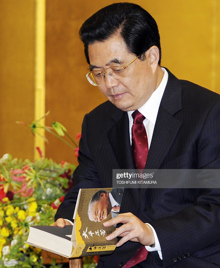 Chinese President Hu Jintao looks at a book on the late Japanese premier Masayoshi Ohira during his meeting with Ohira family at a Tokyo hotel on May 6, 2008. Hu started the first visit by a Chinese leader to Japan in 10 years as the Asian powers ease decades of tension, but hundreds took to the streets to protest over Tibet.