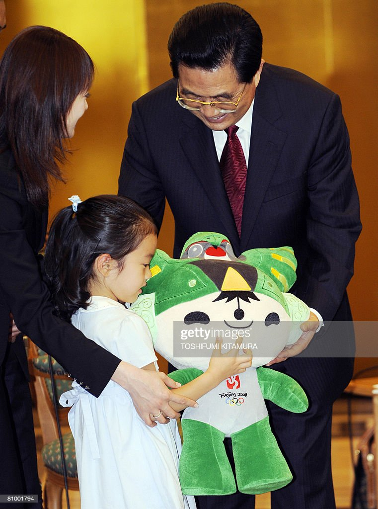 Chinese President Hu Jintao (R) presents a Beijing 2008 Olympics mascot to an unidentified great grand daughter of late Japanese premier Masayoshi Ohira during a meeting with members of Ohira family at a Tokyo hotel on May 6, 2008. Hu started the first visit by a Chinese leader to Japan in 10 years as the Asian powers ease decades of tension, but hundreds took to the streets to protest over Tibet.