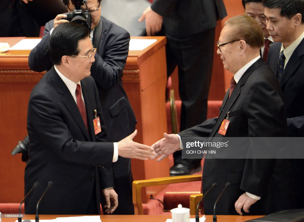 Chinese President Hu Jintao (L) shakes hands with former president Jiang Zemin after the closing of the 18th Communist Party Congress at the Great Hall of the People in Beijing on 14 November 2012. The week-long Communist Party Congress will end with a transition of power to Chinese Vice President Xi Jinping, who will govern for the coming decade amid growing pressure for reform of the communist regime's iron-clad grip on power. AFP PHOTO/GOH CHAI HIN