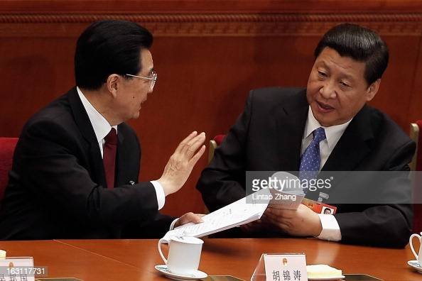 Chinese President Hu Jintao talks with Vice President Xi Jinping after the opening session of the annual National People's Congress at Great Hall of...